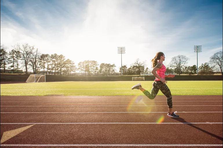 Atleta femenina corriendo en la pista de carreras