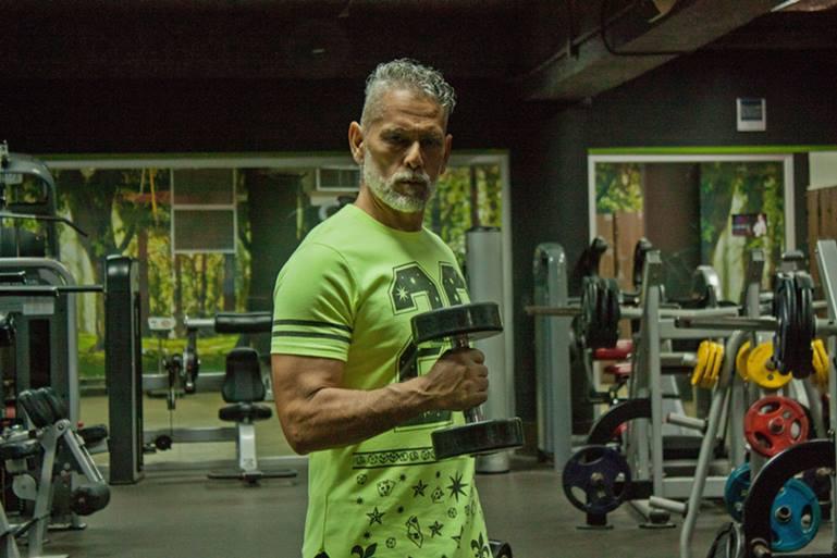Hombre mayor en el gimnasio haciendo pesas
