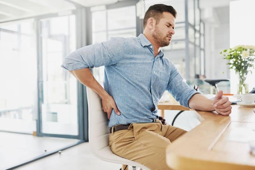 Persona sentada con dolor de espalda