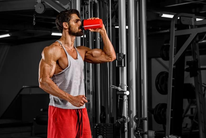 Hombre tomando su aporte nutricional en el gimnasio