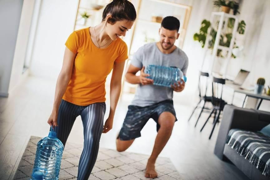 chico-y-chica-entrenando-con-botellas-de-agua-en-casa